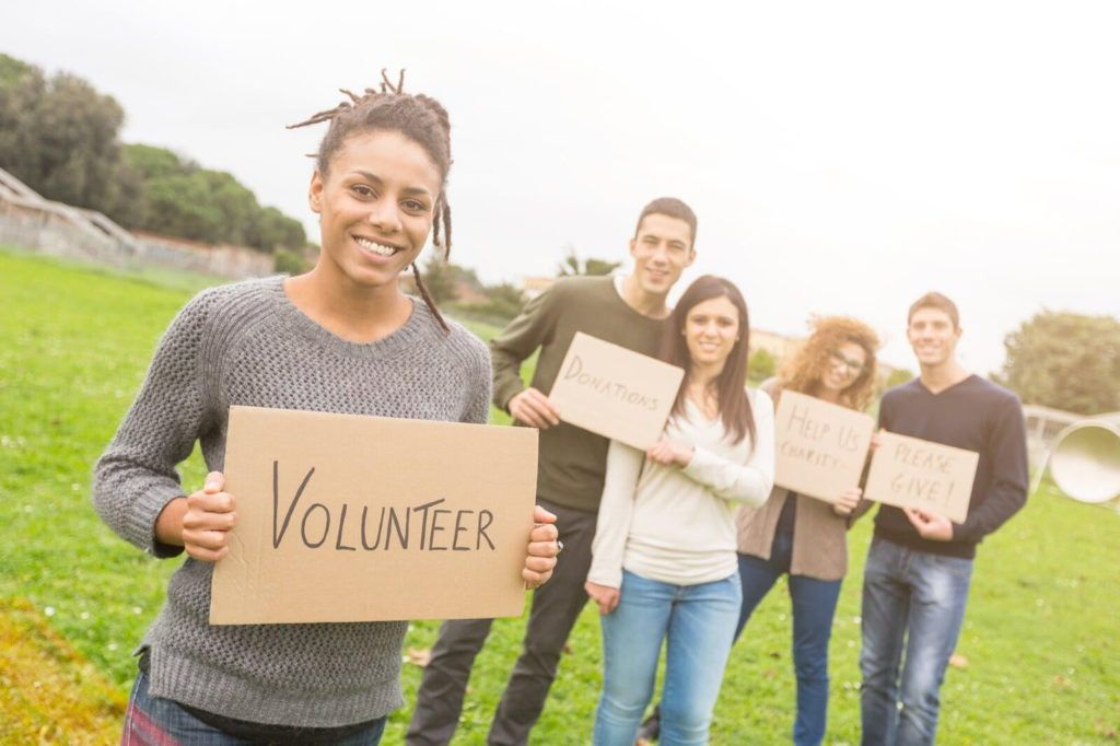 Making parents feel welcome increases the chance they'll volunteer. Picture of adults holding a sign that says, 'Volunteer'.