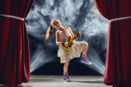 Fundriaising Ideas from Membership Tolokit. Image of a little girl on stage playing guitar at a talent show.