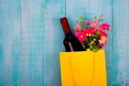 Thank your teachers with puns. Image of a bottle of wine and flowers in a gift bag.